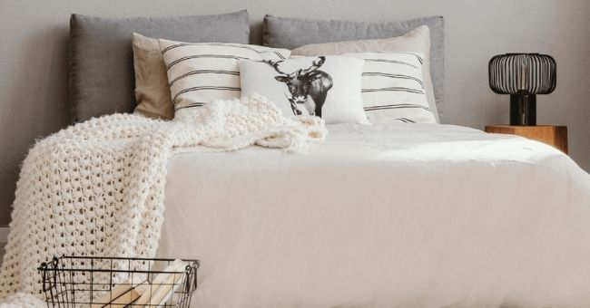 bed with white knitted throw and accent pillows