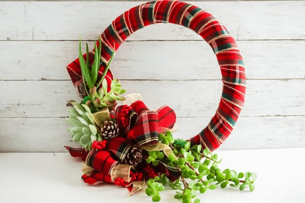 living succulent secured to red plaid wrapped wreath with large red and gold plaid bow