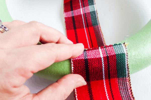 hot glue edge of plaid ribbon to wreath form