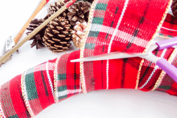 scissors cutting plaid ribbon after wrapped around full wreath form