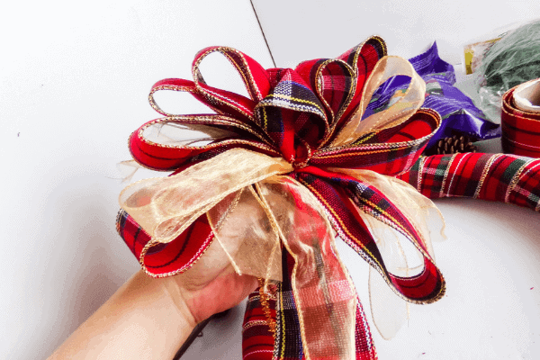 hand holding bow made from red plaid ribbon mixed with gold ribbon