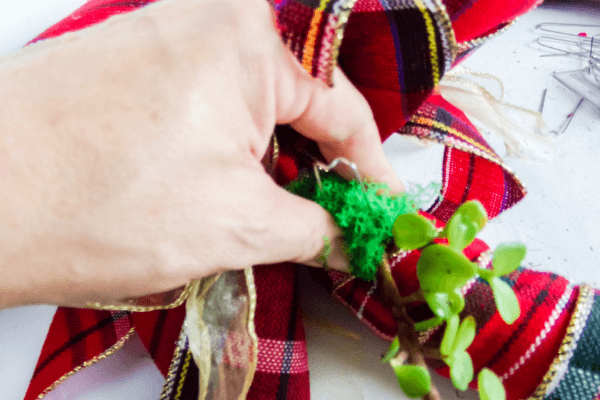 Securing succulent wrapped in moss to wreath form using greening pins