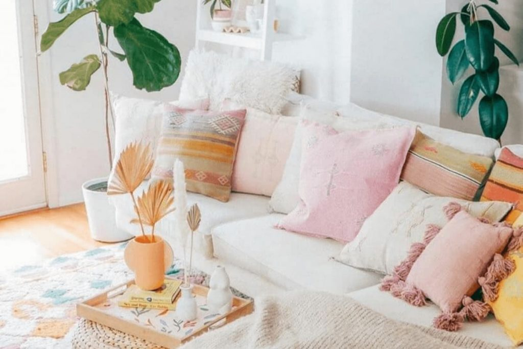 bohemian style living room with white couch filled with pink, white and orange deocrative pillows
