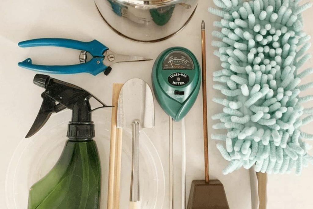 Indoor plant care tools: spray bottle, moisture meter, trowel, pruners, watering can