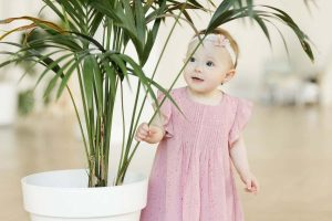baby girl looking at indoor palm plant, one of best plants for a baby nursery