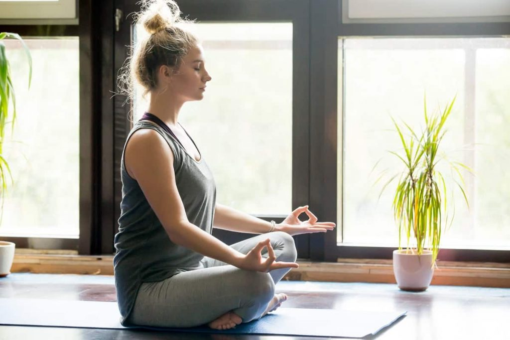 young blonde woman cross legged on yoga mat meditating beside calming indoor plants