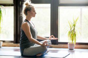 young blonde woman cross legged on yoga mat meditating beside calming indoor plants